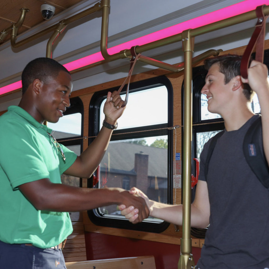 two students shaking hands on the bus